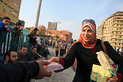 A Muslim woman hands out free sweets to demonstrators in Tahrir Square on day sixteen of the eighteen-day protest against the 30-year rule of Hosni Mubarak. In the background on the left is the Egyptian Museum. (Cairo, Egypt - February 9, 2011)