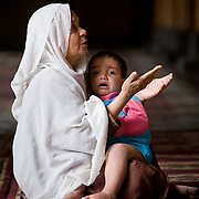 Muslim woman prayers while child cries in her lap.