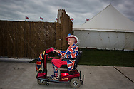 A woman dressed in Union Jack decorated clothing rides her mobility scooter through the grounds of the Goodwood Revival in Chichester, England   Friday, Sept. 9, 2016 The historic motor racing festival celebrates the mid-20th-century golden era of the racing circuit and recreates the atmosphere from the 1950s and 1960s.(Elizabeth Dalziel)