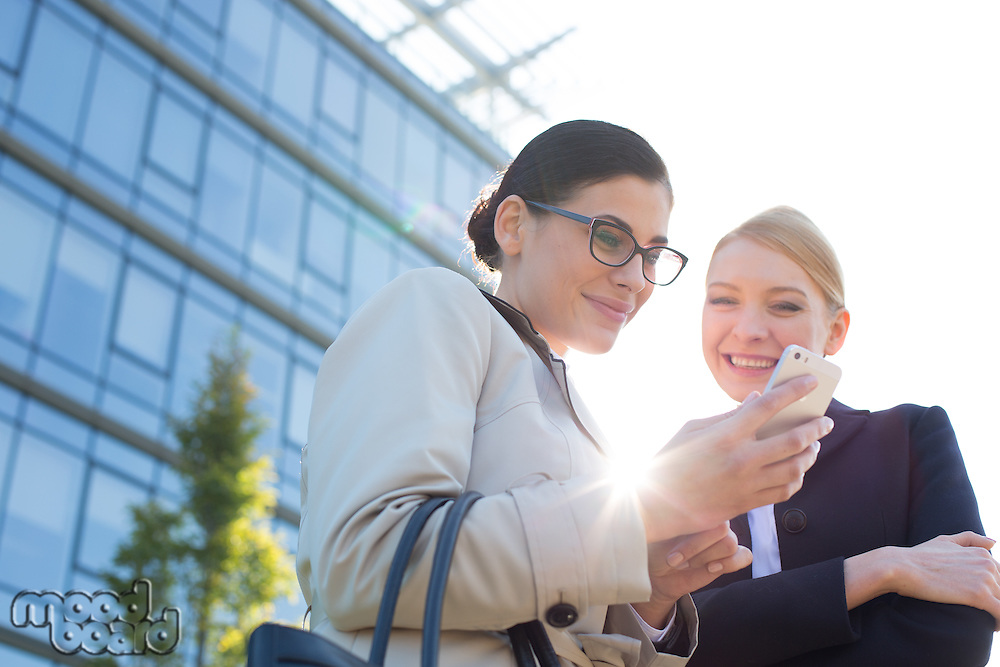 Low angle view of happy businesswomen using smart phone