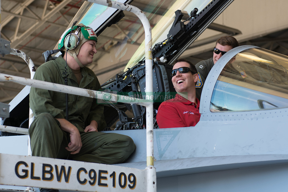 "VIRGINIA BEACH, Va. (Aug. 8, 2018) NASCAR driver Kyle Busch sits in the cockpit of a F/A-18 Super Hornet assigned to the ""Gladiators"" of Strike Fighter Squadron (VFA) 106. Busch visited Naval Air Station Oceana to tour the base, meet fans and sign autographs. (U.S. Navy photo by Mass Communication Specialist Seaman Mark Thomas Mahmod/Released)180808-N-OC333-043"