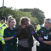 13 local activists locked themselves in specially made arm tubes to block the entrance to Quadrilla's drill site in New Preston Road, July 03 2017, Lancashire, United Kingdom. Medics attending an activist hurt by police. The 13 activists included 3 councillors; Julie Brickles, Miranda Cox and Gina Dowding and Nick Danby, Martin Porter, Jeanette Porter,  Michelle Martin, Louise Robinson,<br /> Alana McCullough, Nick Sheldrick, Cath Robinson, Barbara Cookson, Dan Huxley-Blyth. The blockade is a repsonse to the emmidiate drilling for shale gas, fracking, by the fracking company Quadrilla. Lancashire voted against permitting fracking but was over ruled by the conservative central Government. All the activists have been active in the struggle against fracking for years but this is their first direct action of peacefull protesting. Fracking is a highly contested way of extracting gas, it is risky to extract and damaging to the environment and is banned in parts of Europe . Lancashire has in the past experienced earth quakes blamed on fracking.