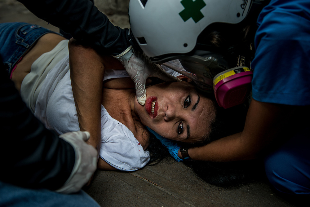 "CARACAS, VENEZUELA - JUNE 3, 2017:  Medical students evacuate a woman that was having multiple, uncontrollable seizures and drifting in and out of consciousness after being heavily tear gassed by security forces during a peaceful protest.  Hundreds of medical students volunteer on the front line of clashes as ""Green Helmets"" - first responders that evacuate and give first aid to injured protesters.  Many young medical students are angry about the poor state of the public healthcare system.  Over 85 percent of medicines are either impossible, or very difficult to find in Venezuela.  Public hospitals face shortages of even the most basic supplies, like gauze, latex gloves, syringes - even running water. Many say they see volunteering with the Green Helmets as using their talents to supporting the protest movement taking over the streets of Caracas. PHOTO: Meridith Kohut"