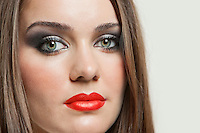 Detail shot of attractive young woman with bright red lips against gray background