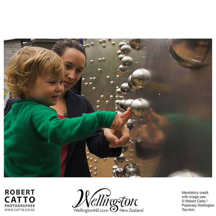 A mother & child enjoy counting the dots on the braille-based sculpture 'Invisible City', by Anton Parsons, in downtown Wellington New Zealand.