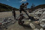 RENDEL, HAITI - OCTOBER 12, 2016: A local man bathes his daughters in the river that runs along the village of Rendel, and is believe to be contaminated and spreading Cholera. A week has passed since Hurricane Matthew tore through this remote stretch of Haiti's southern peninsula, leaving an apocalyptic landscape of treeless countryside, disarticulated homes and a land stripped of its natural riches.  But for many, the torment has only started.  What began as a small cholera outbreak in the mountains before the hurricane has now spread into every crevice of this valley and the hills above. First came the sick, who trudged down to Rendel in search of medical care, bringing the disease with them. Then, when the floods came, cholera was carried down by the water itself, which swept up fecal matter dumped on the hillsides, contaminating the river and other drinking supplies.  Water unboiled or unchlorinated and poor hygiene meant the infections spread rapidly.  PHOTO: Meridith Kohut for The New York Times