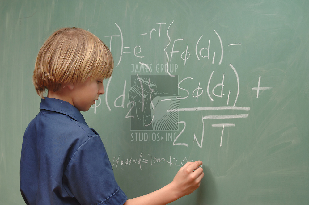 Nine year old boy doing advanced math on a chalkboard