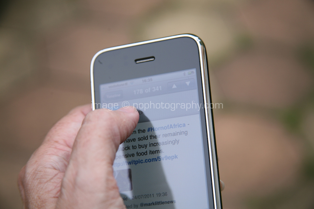 Close-up of a person using twitter on an iPhone