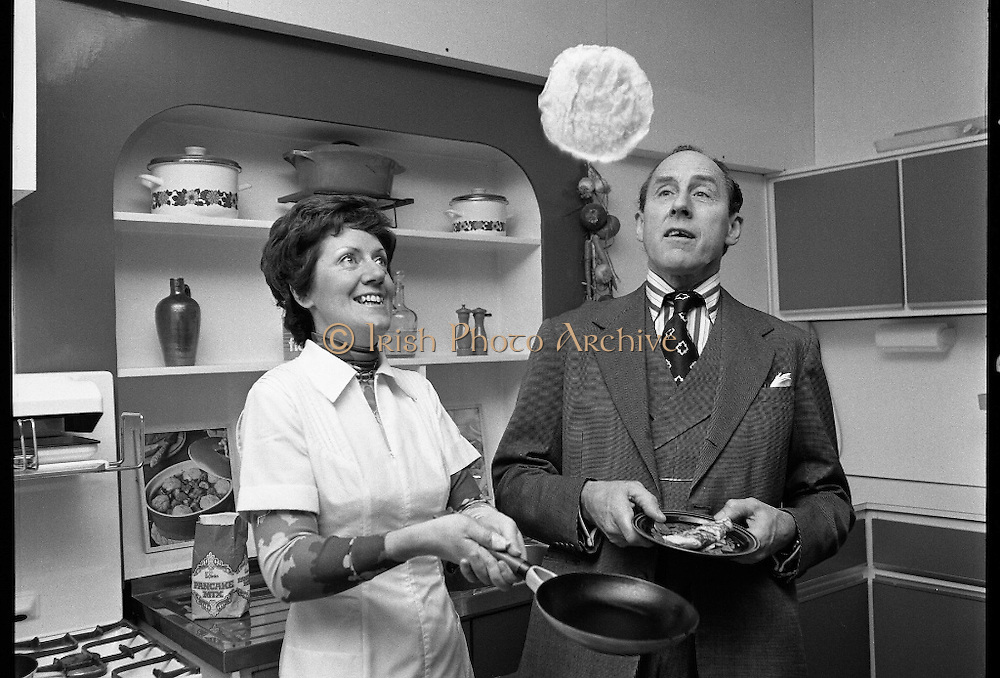 Pancake making At Ranks.   (K91)..1977..22.02.1977..02.22.1977..22nd February 1977..At Ranks experimental kitchen in Phibsborough, Dublin,Shiela Cunningham,Chief Adviser of Ranks Home Baking Service made the first pancakes of the day, today being Pancake Tuesday. While making the pancakes Ms Cunningham was surprised when an unexpected visitor dropped in. Mr Joseph Rank ,Chairman of the company ,called in to sample the first pancake of the day. He was in Dublin for the company's Annual General Meeting..Mr Joseph Rank pictured trying his hand at tossing pancakes..Image of Mr Rank looking on as Shiela Cunningham tosses a pancake high in the air.