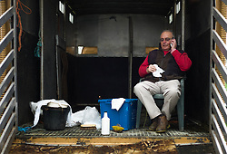 © Licensed to London News Pictures. <br /> 20/09/2014. <br /> <br /> Stokesley, England<br /> <br /> A man sits in the back of his horse box sheltering from rain during the Stokesley Agricultural Show in North Yorkshire, England. The show which dates back to 1859 is the largest one day agricultural show in the north of England.<br /> <br /> Photo credit : Ian Forsyth/LNP