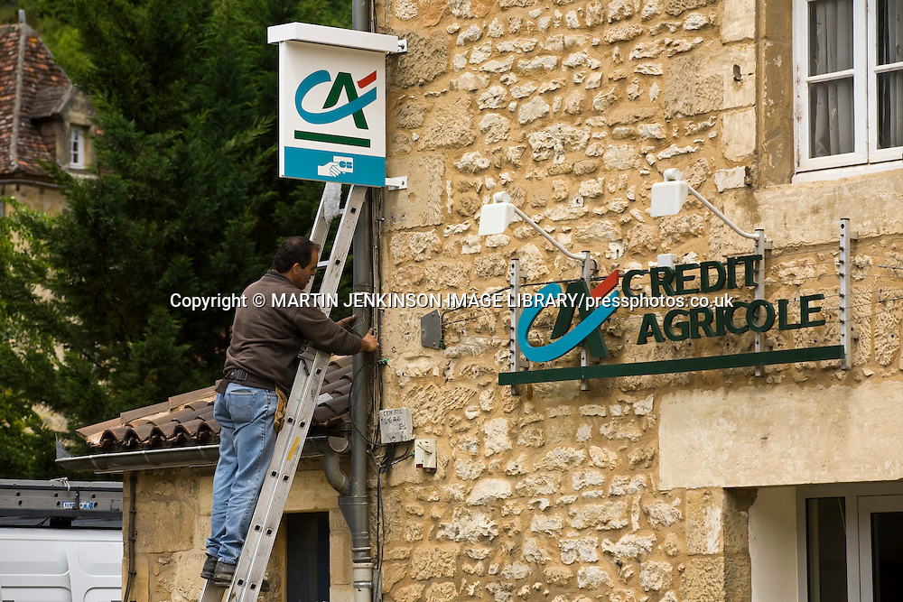 Electrician working up a ladder on a Credit Agricole bank sign