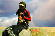 female Bedouin shepherd in the field on a stormy day with a rainbow in the background
