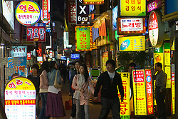 Many illuminated signs outside bars and restaurants on a street in Nampo nightlife district of Busan in South Korea