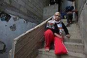 Palestinian woman Safa Fayez , 29 , as she pulls herself up the stair case of her home and her son carries her shoe in Beit Hanoun ,Gaza  December 11,2014 . She was seriously wounded by shrapnel during last summer's war in Gaza between Israel and the Palestinian militants in the Hamas controlled Gaza Strip when  IDF shells hit the UN school crowded by hundreds of Palestinians seeking shelter . The attack on July 24,2014 killed at 15 Palestinians and wounded many including her baby and husband . She is a mother of four children and said that she had just left the classroom she was staying in with her family and heading outside to wait for a bus that the Red Cross was providing to evacuate the displaced to a safer area when the attack occurred . (Photo by Heidi Levine/Sipa Press).