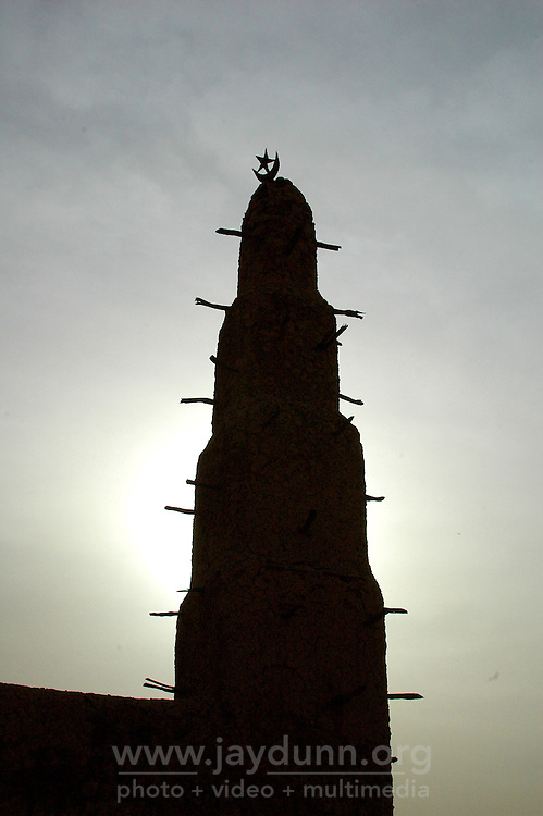 BURKINA FASO, Bani, 2007. The sun dips behind a mosque's minaret atop the flats overlooking Bani village.