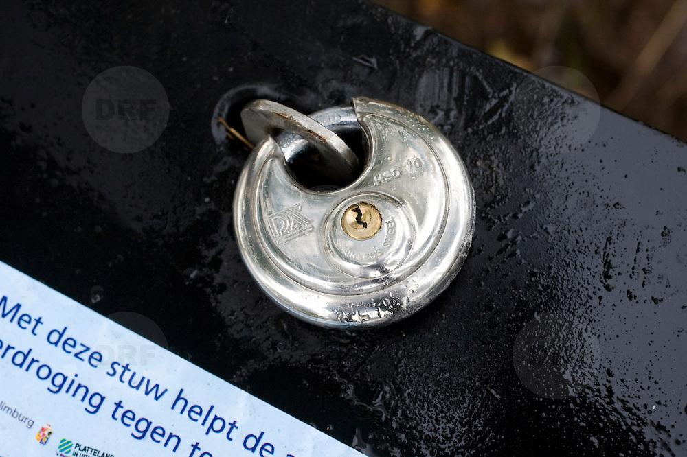 """Nederland Kronenberg 30 september 2008 20080930 Foto: David Rozing ..Serie vernattingscampagne """" Nieuw Limburgs Peil """" de Peel ..Slot van stuw, om diefstal van onderdelen te voorkomen. Vernattingscampagne """" Nieuw Limburgs Peil """" in omgeving de Peel, uitgevoerd door o.a. de  plaatselijke boeren in samenwerking met het waterschap Peel en Maasvallei. Het doel is een hoger peil van het grondwater dmv het vasthouden van hemelwater. Dit  wordt verwezenlijkt door de aanleg van stuwen in de watergangen bij bv akkers. Door de stuwen in de sloten/ watergangen dicht te zetten wordt het grondwaterpeil hoger in het gebied. Voordelen hiervan zijn: verdroging van de natuur wordt tegen gegaan, voor de boeren kan het drie beregeningen per jaar besparen. Boerenpeil: 400 van de inmiddels 1250 stuwen worden beheerd door de boeren. Natuurgebieden als De Grote Peel en Maria peel hebben veel te lijden gehad onder eerder .waterbeheer:  Het waterschap heeft in het verleden veel akkerslootjes, beken en kanaaltjes aangelegd om ervoor te zorgen dat het water rond dit natuurgebied snel kon wegvloeien, zodat de oogsten.niet zouden verrotten en de akkers goed bewerkbaar waren, maar waardoor nu het waterpeil erg snel zakt..Medewerkers van het waterschap bezoeken de boeren thuis en voeren keukentafelgesprekken met hen om ze te betrekken bij het project. .De Peel is een grotendeels verdwenen hoogveengebied op de grens van de Nederlandse provincies Noord-Brabant en Limburg. ..Foto David Rozing"""