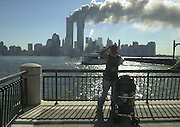 A pedestrian with a stroller stops on the Jersey City waterfront to take a picture of the World Trade Center on fire.