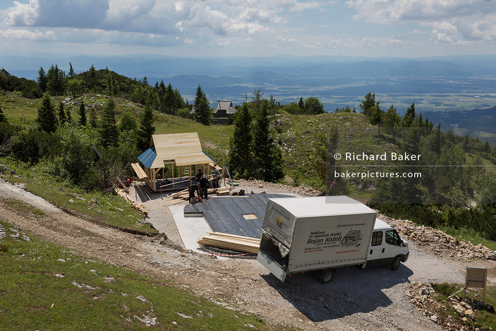 Construction of a new Slovenian holiday mountain hut in the style of a herders' shelter in Velika Planina, on 26th June 2018, in Velika Planina, near Kamnik, Slovenia. Velika Planina is a mountain plateau in the Kamnik–Savinja Alps - a 5.8 square kilometres area 1,500 metres (4,900 feet) above sea level. Otherwise known as The Big Pasture Plateau, Velika Planina is a winter skiing destination and hiking route in summer. The herders' huts became popular in the early 1930s as holiday cabins (known as bajtarstvo) but these were were destroyed by the Germans during WW2 and rebuilt right afterwards by Vlasto Kopac in the summer of 1945.