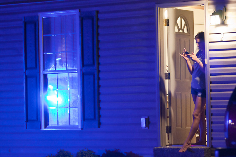 May 19, 2012 A woman stands in a doorway after a young female was arrested for drunk driving. The driver of the SUV caused damage to three properties before rolling into another vehicle on Blue Lick Road in Brooks, KY.