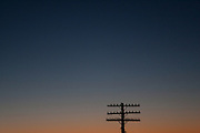 Sitting birds dot the top of a power cable post in the foreground of a Virginia sunset.
