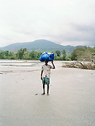Man carrying a bundle in his head on North Andaman Island beach