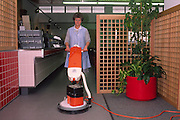 Local authority cleaner using a rotary buffer to polish the floor in a college refectory ....