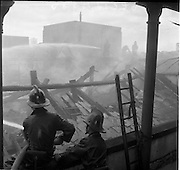 05/07/1961<br /> 07/05/1961<br /> 05 July 1961<br />  A fire at Powers Distillery, John's Lane, Dublin. The fire fortunately occurred during a period when the distillery was not in use, but a warehouse containing 4000 hogsheads of maturing whiskey was destroyed. Picture shows Firemen bringing the blaze under control.