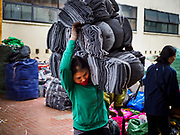 "22 DECEMBER 2017 - HANOI, VIETNAM: A woman carries a bundle of sweat pants in the wholesale clothes and fabric section of Dong Xuan Market in the old quarter of Hanoi. The old quarter is the heart of Hanoi, with narrow streets and lots of small shops but it's being ""gentrified"" because of tourism and some of the shops are being turned into hotels and cafes for tourists and wealthy Vietnamese.    PHOTO BY JACK KURTZ"