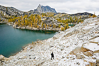 A view of a woman descending a talus field toward Inspiration Lake with Prusik Peak off in the distance, Enchantment Lakes Wilderness Area, Washington Cascades, USA.