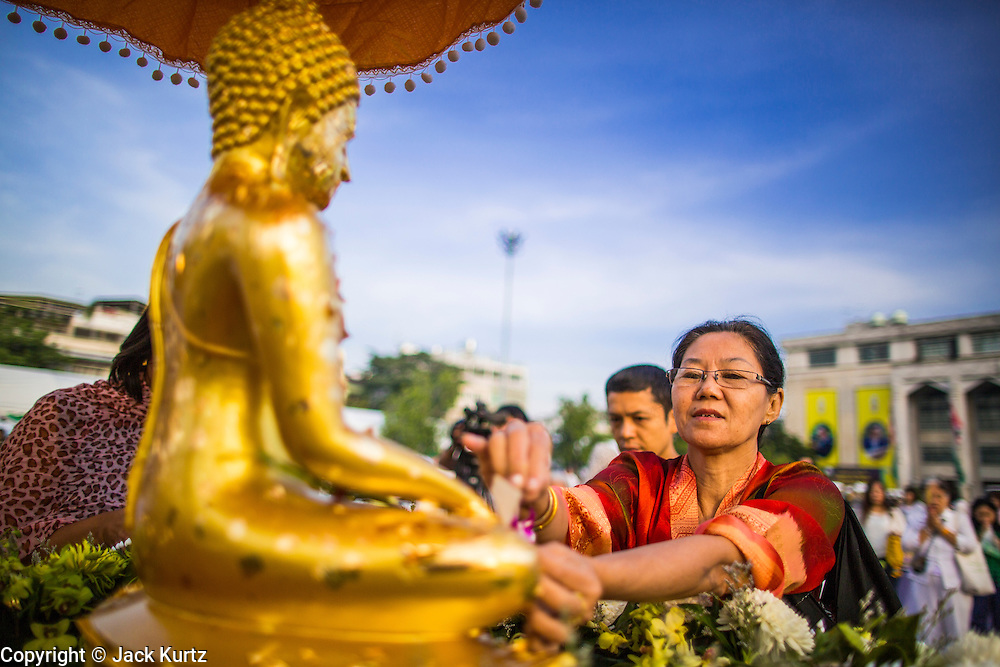 "01 JANUARY 2013 - BANGKOK, THAILAND: A woman applies gold leaf to a statue of the Buddha during a special merit making ceremony at Bangkok City Hall New Year's morning. Many Thais go to Buddhist temples and shrines to ""make merit"" for the New Year. The traditional Thai New Year is based on the lunar calender and is celebrated in April, but the Gregorian New Year is celebrated throughout the Kingdom.      PHOTO BY JACK KURTZ"