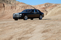 Rolls Royce car parked on unpaved road with mountains in background