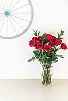 Two dozen red roses set against a neutral cream colour wall with a rustic yet charming wheel decoration on the wall.