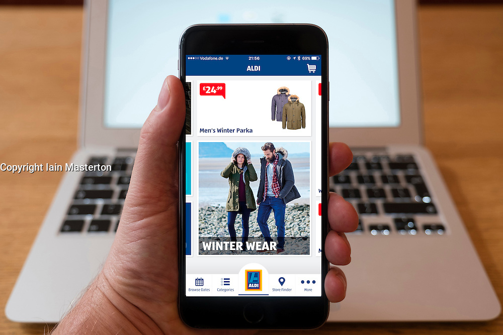 Using iPhone smartphone to visit mobile online clothes  store of Aldi discount supermarket