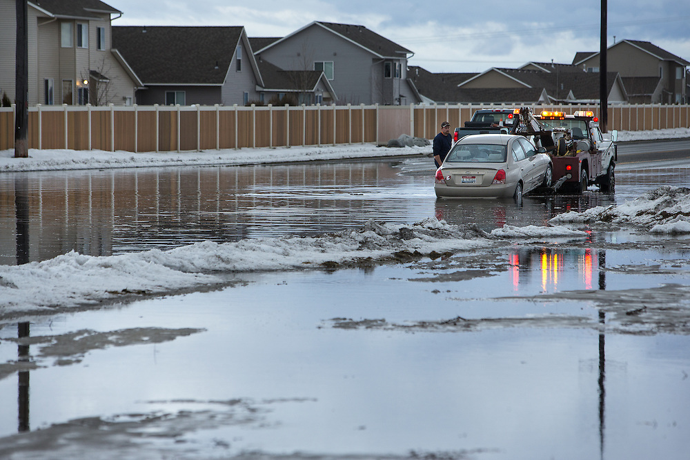 GABE GREEN/Press<br /> <br /> A car is hooked up to a tow truck after getting stuck in the middle of a large puddle that formed on Prairie Avenue between Atlas and Huetter Road in Coeur d&rsquo;Alene Wednesday when rapid snow melt mixed with rain caused flooding around the area.