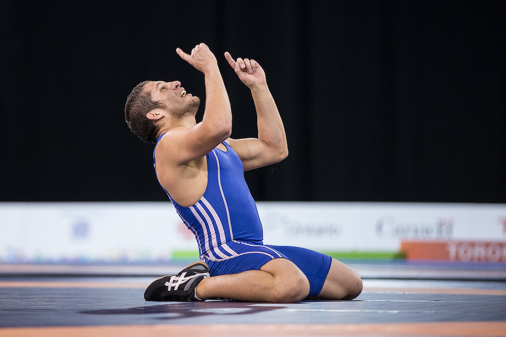 Cristobal Torres of Chile celebrates his win over Dylan Williams of Canada in the bronze medal bout of the 59kg weight class of the men's greco-roman wrestling at the 2015 Pan American Games in Toronto, Canada, July 15,  2015.  AFP PHOTO/GEOFF ROBINS