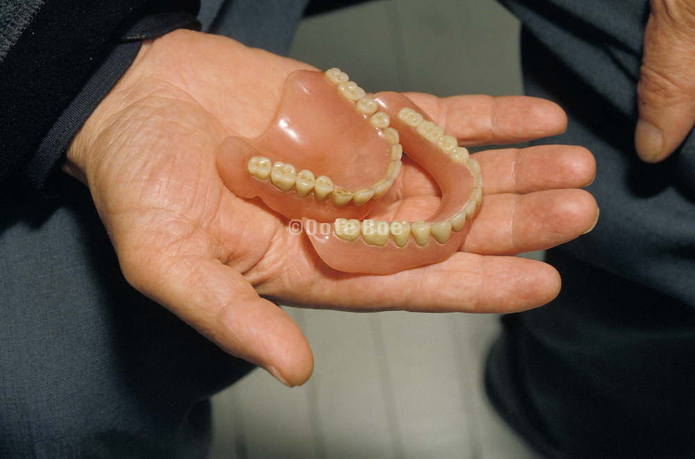 Man holding his artificial teeth