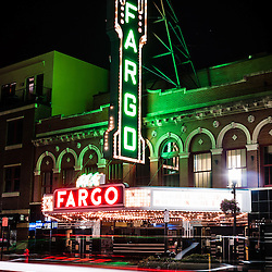 Photo of Fargo ND theater at night with motion blurred car lights along North Broadway Drive. The Fargo Theatre was built in 1926 and is on the National Register of Historic Places. The Fargo Theatre is currently a popular venue for films, movies, concerts, plays and other live events. Photo is vertical and was taken in 2011.