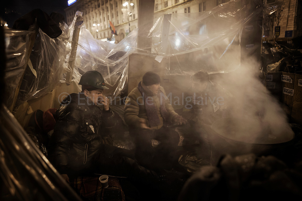Protesters warm themselves as they stand guard on one of the barricades surrounding Maidan square that is occupied by the protesters. Thousands of people have been protesting against the government since a decision by Ukrainian president Viktor Yanukovych to suspend a trade and partnership agreement with the European Union in favor of incentives from Russia. 08 December 2013.