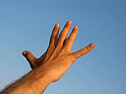 Man's hand reaches out to a blue sky