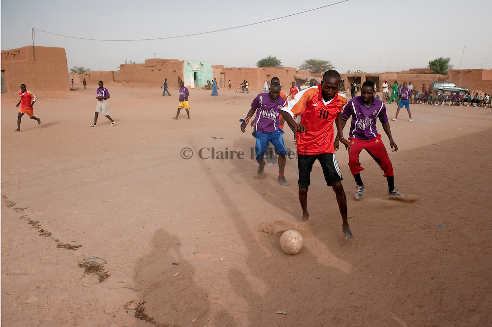 Oumaru, a young african migrant from Burkina Faso playing  football in Agadez.