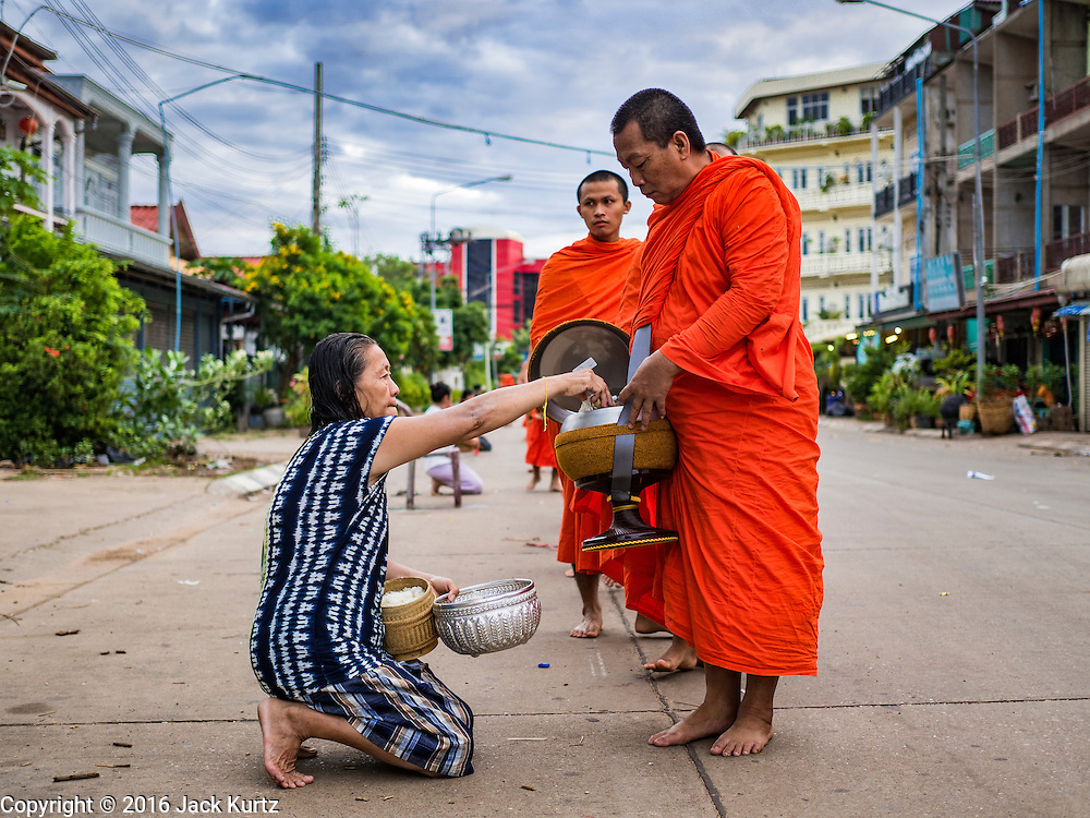 16 JUNE 2016 - PAKSE, CHAMPASAK, LAOS:  A woman drops food into monks' bowls on the monks' morning Tak Bat, or alms rounds in Pakse. The monks walk through the community just after sunrise accepting alms from people. Pakse is the capital of Champasak province in southern Laos. It sits at the confluence of the Xe Don and Mekong Rivers. It's the gateway city to 4,000 Islands, near the border of Cambodia and the coffee growing highlands of southern Laos.     PHOTO BY JACK KURTZ
