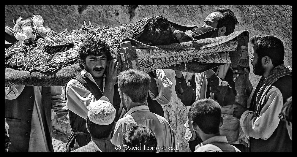 "In this ""Signature Series"" images by David Longstreath, mourners gather outside Kabul, Afghanistan in September 2002, to bury a young man killed the day before in a car bombing. At least 21 others died when a car bomb as set off in a busy market area of downtown Kabul. The man was the sole support for his family."