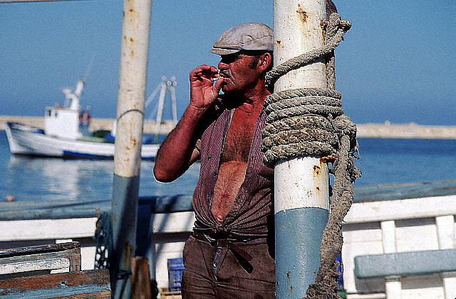 ca. October 1991, Alicante, Spain --- A fisherman takes a moment to smoke a cigarette. Spain. --- Image by © Owen Franken/CORBIS
