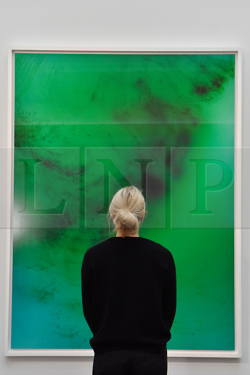 """© Licensed to London News Pictures. 12/10/2017. London, UK.  A staff member views """"Freischwimmer 193"""", 2009, by Wolfgang Tillmans (Est. GBP120-180k) at a preview of artworks for the """"Art for Grenfell"""" auction taking place at Sotheby's, New Bond Street, on 16 October.  Leading contemporary artists have agreed to donate works to the auction, the proceeds of which will be divided equally amongst the 158 surviving families of the Grenfell Tower fire by the Rugby Portobello Trust charity. Photo credit : Stephen Chung/LNP"""