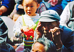 China, Taiyuan, 2008. Free for the whole neighborhood, rapt residents watch all-day Chinese opera performances during the September full moon day.