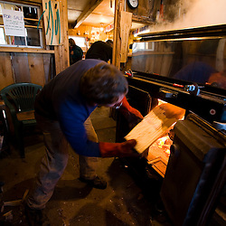 Keith Fifield loads wood into the fire under the sap evaporator at Fifield's Sugarhouse in Strafford, Vermont.