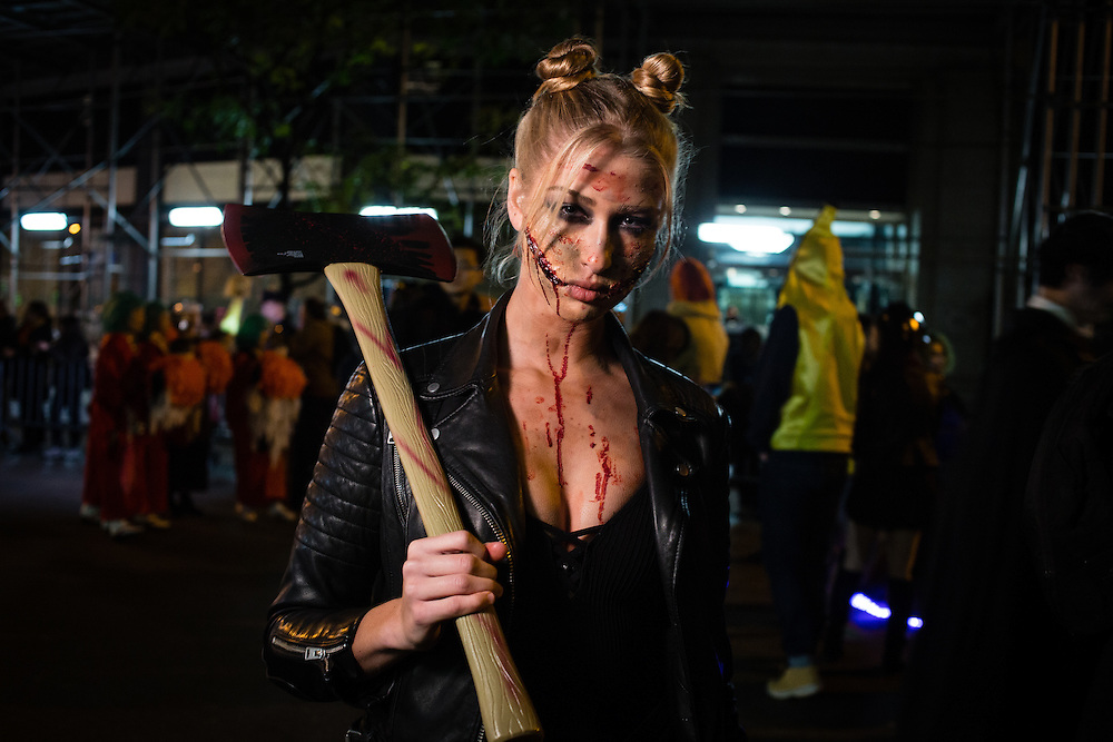 New York, NY - 31 October 2016. A woman with bloody wounds carries an axe  in the Greenwich Village Halloween Parade.