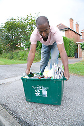 Man placing curb side recycling collection box on the pavement ready for collection,