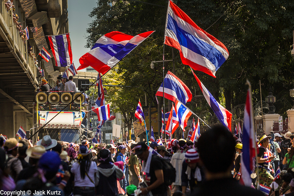 "14 JANUARY 2014 - BANGKOK, THAILAND:  Anti-government protestors wave Thai flags on Rama I Road in front of Royal Thai Police headquarters. Hundreds of protestors picketed police headquarters because they accuse the police of siding with the government during the protests. Tens of thousands of Thai anti-government protestors continued to block the streets of Bangkok Tuesday to shut down the Thai capitol. The protest, ""Shutdown Bangkok,"" is expected to last at least a week. Shutdown Bangkok is organized by People's Democratic Reform Committee (PRDC). It's a continuation of protests that started in early November. There have been shootings almost every night at different protests sites around Bangkok, but so far Shutdown Bangkok has been peaceful. The malls in Bangkok are still open but many other businesses are closed and mass transit is swamped with both protestors and people who had to use mass transit because the roads were blocked.    PHOTO BY JACK KURTZ"