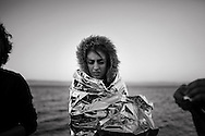 A woman is wrapped with a warm blanket as refugees and migrants riding a dinghy reach the shores of the Greek island of Lesbos after crossing the Aegean Sea from Turkey on November 12, 2015.